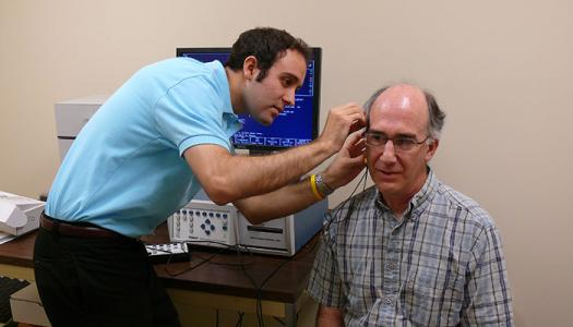 Audiology clinic student examines patient