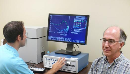 An audiologist checks hearing of a patient