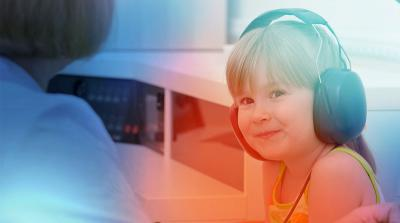 smiling 5-year-old boy wearing headphones