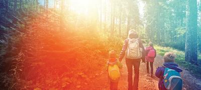 parent hiking with 3 children