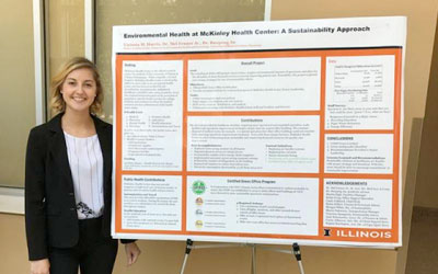 student standing in front of large informational poster